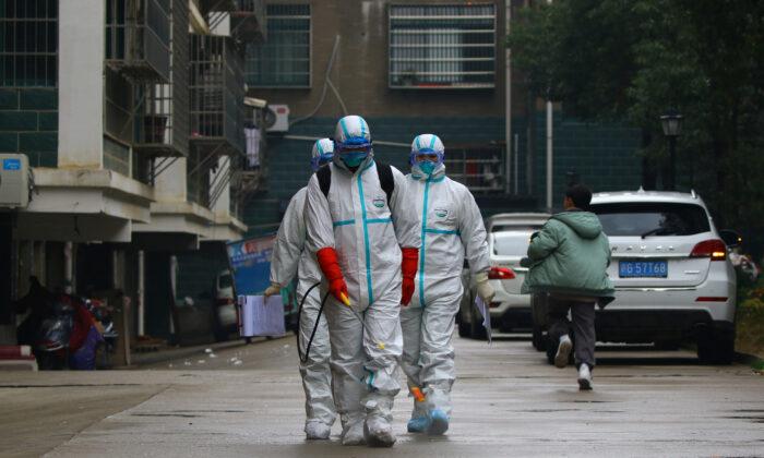 중국 장시성 루이창에서 신종 코로나바이러스 발생 후, 보호복을 입은 현지 보건당국의 직원들이 주택가를 소독하고 있다. 2020. 1. 25. | cnsphoto via Reuters=연합뉴스