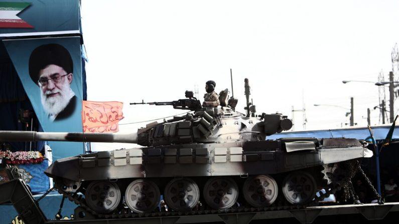 2015년 4월 18일 테헤란에서 열린 열병식에서 이란 최고지도자 알리 하메네이(Ali Khamenei)의 초상화 옆을 T-72 탱크에 탑승한 군인이 지나고 있다.  | BEHROUZ MEHRI/AFP via Getty Images