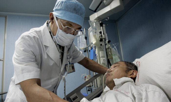 중국 최고 중증급성호흡기증후군(SARS) 전문가인 중난산이 중국 남부 광둥(廣東)성 광저우(廣州) 호흡기 질병연구소 감염 병동에서 환자 중 한 명을 살피고 있다. 2005. 6. 10. | Goh Chai Hin/AFP via Getty Images=연합뉴스