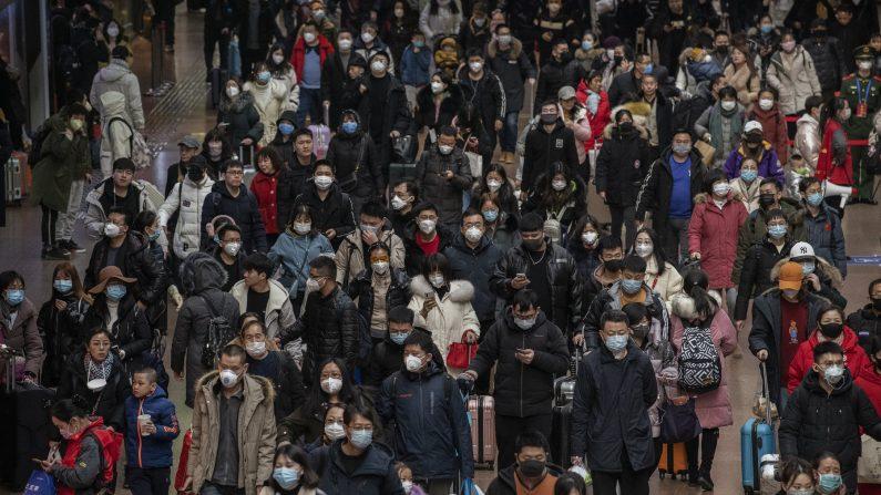우한 폐렴 발생 이후 베이징의 기차역에서 이용객들이 대부분 마스크를 착용한 채 이동하고 있다. 중국 정부는 중국 중부를 중심으로  여행 제한 조치를 내렸다. | Kevin Frayer/Getty Images
