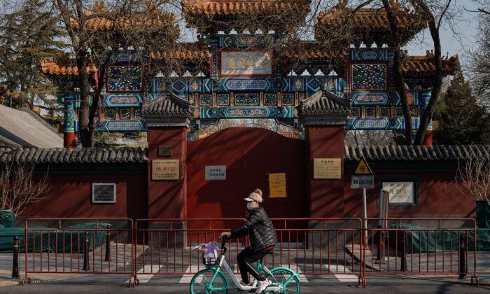 신종 코로나바이러스 감염으로부터 보호하기 위해 마스크를 쓴 여성이 자전거를 타고 중국 베이징에 있는 라마 사원 앞을 지나간다. 2020. 2. 23. | NICOLAS ASFOURI/AFP via Getty Images