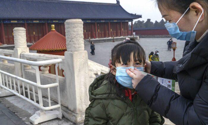 한 중국 여성이 중국 설인 춘절 연휴 동안 문을 연 중국 베이징 톈탄(天壇)구내를 둘러보며 어린아이에게 보호 마스크를 씌우고 있다. 2020. 1. 27. | Kevin Frayer/Getty Images