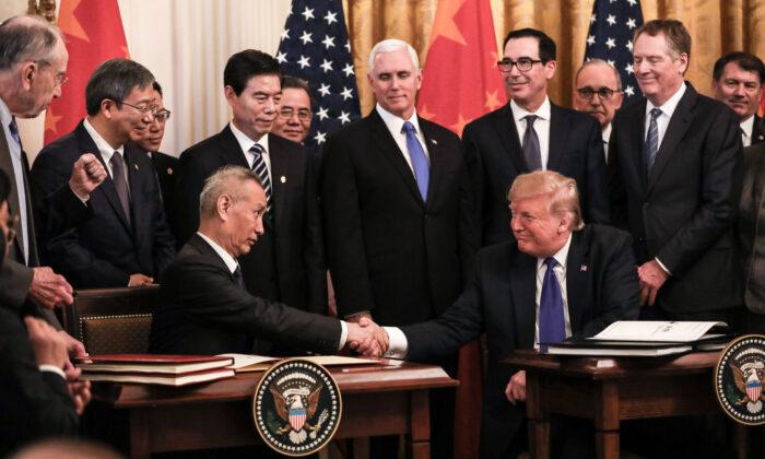 워싱턴 백악관 이스트룸에서 류허 중국 부총리(왼쪽)와 도널드 트럼프 미국 대통령이 1단계 합의서에 서명하며 관계자들에게 둘러싸여 있다. 2020. 1. 15. | Charlotte Cuthbertson/The Epoch Times