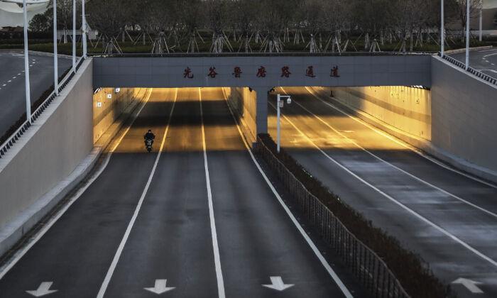 중국 우한 옵티컬밸리 빈 거리에 한 남성이 자전거를 타고 있다. 2020. 2. 16. | Getty Images