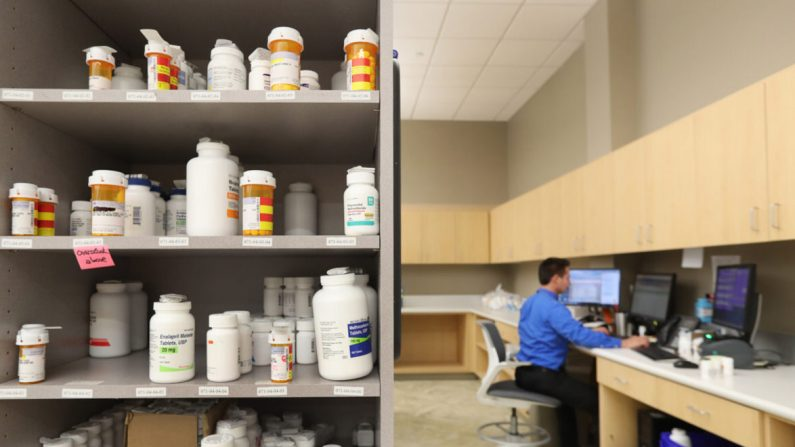유타주 미드베일의 인터마운틴 헬스케어 중앙 약국 선반에 약병이 놓여 있고, 약국 직원이 컴퓨터로 작업하고 있다. 2018. 9. 10. | George Frey/Getty Images