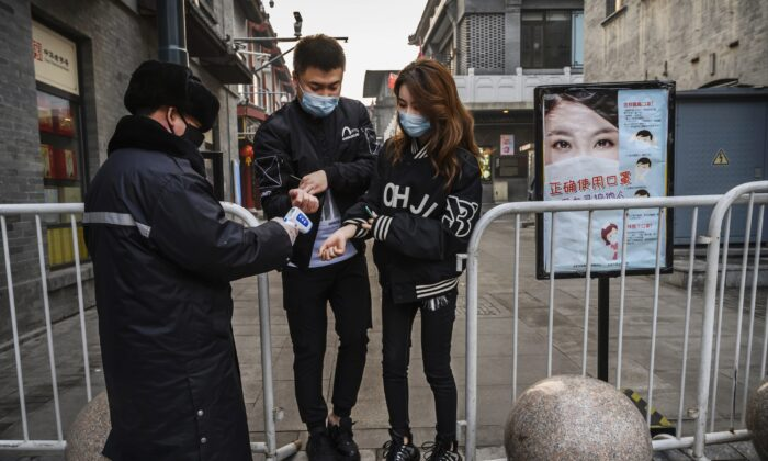 중국 공안이 거의 텅 비어 있는 베이징 상업가로 들어서는 두 사람의 체온을 재고 있다. 2020. 2. 12   Kevin Frayer/Getty Images