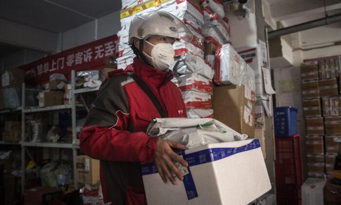 중국 후베이성 우한 배송센터에서 직원이 배송 물품을 운반하고 있다. 2020. 1. 20. | Stringer/Getty Images