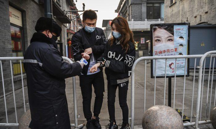 중국 공안이 중국 베이징의 거의 텅 빈 상가로 들어서는 사람의 체온을 재고 있다. 2020. 2. 12.   Kevin Frayer/Getty Images
