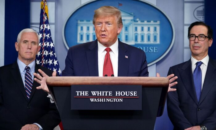 도널드 트럼프 미국 대통령이 워싱턴 백악관에서 중공 바이러스 사태와 관련해 기자회견을 하고 있다. 오른쪽에 스티븐 므누신 재무장관, 왼쪽에 마이크 펜스 부통령이 함께 서 있다. 2020. 3. 25. | Mandel Ngan/AFP via Getty Images