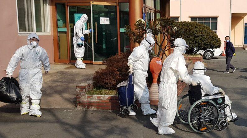 2울 22일 경북 청도 대남병원에 입원 중이던 한 환자가 휠체어를 타고 이송되고 있다.   연합뉴스