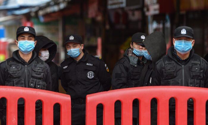 우한시 화난 수산시장 밖에 경찰관과 경비원들이 서 있다. 2020. 1. 24. | HECTOR RETAMAL/AFP via Getty Images