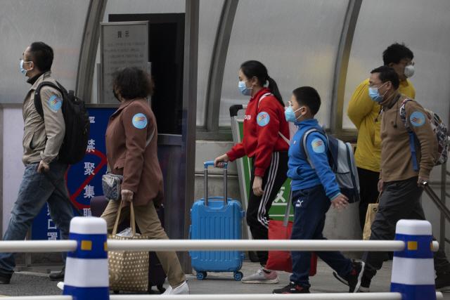 중국 후베이성을 출발한 시민들이 26일 베이징 서역에 도착해 이동하고 있다. 중국은 코로나19 확산 저지를 위해 발병지인 후베이성에 내렸던 봉쇄령을 25일부터 해제했다. | AP연합