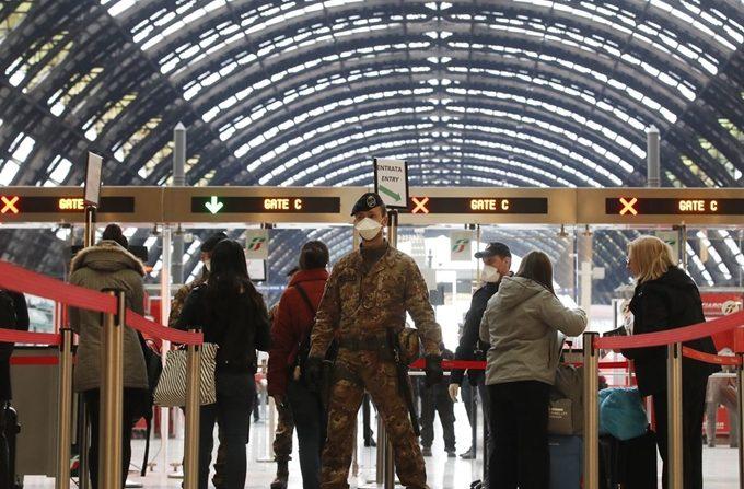 코로나19 확산 방지를 위해 전국이동제한 명령이 내려진 가운데 9일 밀라노 중앙역에서 경찰과 군인들이 승객들을 검문하고 있다.   밀라노=AP 연합뉴스