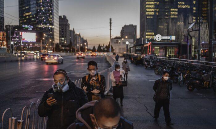 베이징시에서 통근하는 사람들이 마스크를 쓰고 버스를 기다리며 줄서 있다. 2020. 3. 20   Kevin Frayer/Getty Images