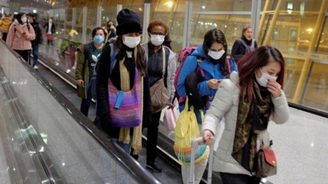 25일 중국 베이징 공항에 도착한 여행객들이 마스크를 쓴 채 에스컬레이터를 타고 이동하고 있다. | 로이터=연합뉴스
