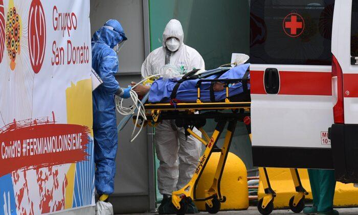의료진이 이탈리아 적십자 구급차에서 밀라노 산 라파엘 병원 밖 스포츠 센터에 설치된 중환자실로 환자를 옮기고 있다. 2020. 3. 23. | Miguel Medina/AFP via Getty Images