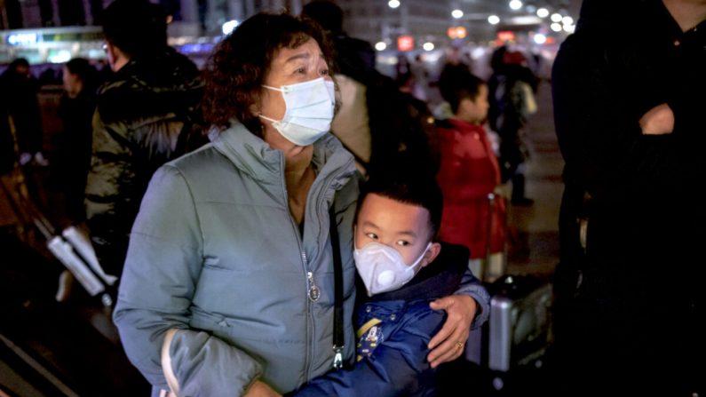 2020년 1월 21일 중국 베이징 철도역에서 한 소년이 열차에 탑승 전 친척을 껴안고 있다. | Kevin Frayer/Getty Images