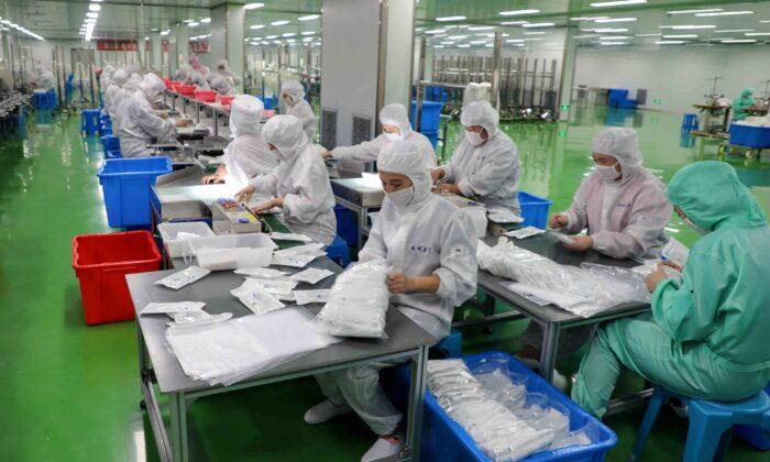 중국 산둥 성의 빈저우시에 있는 한 공장에서 근로자들이 방호복을 만들고 있다. 2020.2.13. | STR/AFP/Getty Images