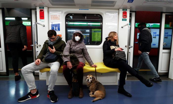이탈리아 밀라노 지하철에 마스크를 쓴 여성과 개가 앉아 있다. 2020. 3. 1. | 로이터=연합뉴스