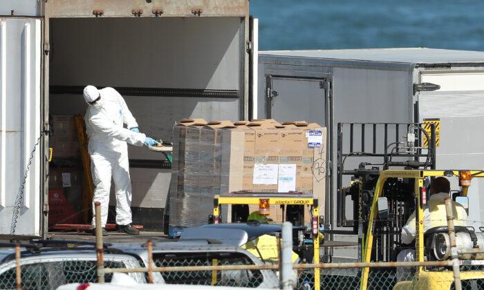 호주 프리맨틀 여객터미널에서 방호복을 입은 노동자들이 MSC 매그니피카호에 실을 물건을 트럭에서 내리고 있다. 2020. 3. 24. |Paul Kane/Getty Images
