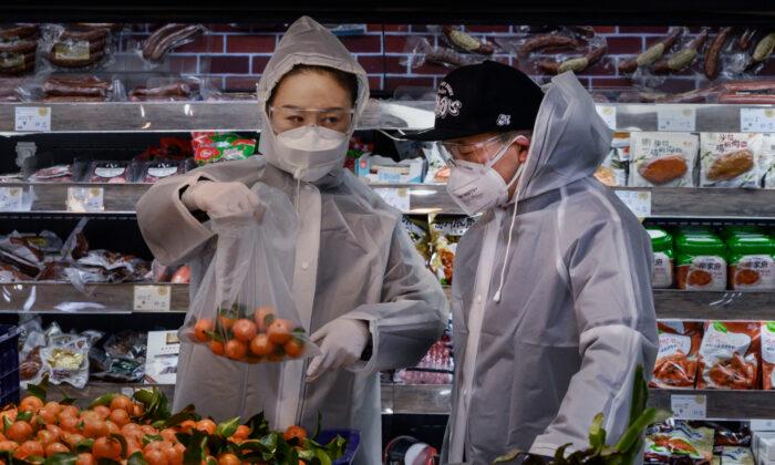 한 중국 커플이 비닐 코트와 마스크, 고글을 착용한 채 베이징에 있는 슈퍼마켓에서 장을 보고 있다. 2020.2.11.  Kevin Frayer/Getty Images