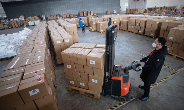 중국 우한의 한 전시센터 창고에서 의료용품을 옮기고 있는 직원과 자원봉사자들. 2020. 2. 4. | STR/AFP via Getty Images