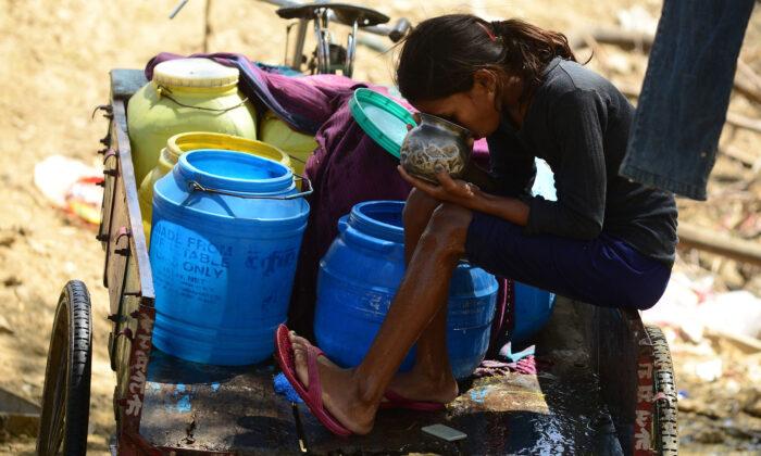 인도 알라하바드에서 한 소녀가 인력거 트롤리에 앉아 플라스틱 통으로 도로변 수도꼭지에서 받은 물을 마시고 있다. 2016. 3. 22. | SANJAY KANOJIA/AFP via Getty Images