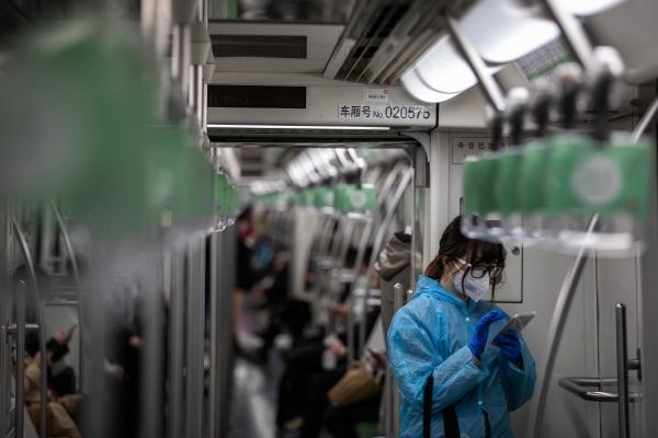마스크와 장갑, 우비를 착용한 여성이 중국 상하이 지하철에서 휴대전화를 사용하고 있다. 2020.2.24   상하이=EPA연합뉴스