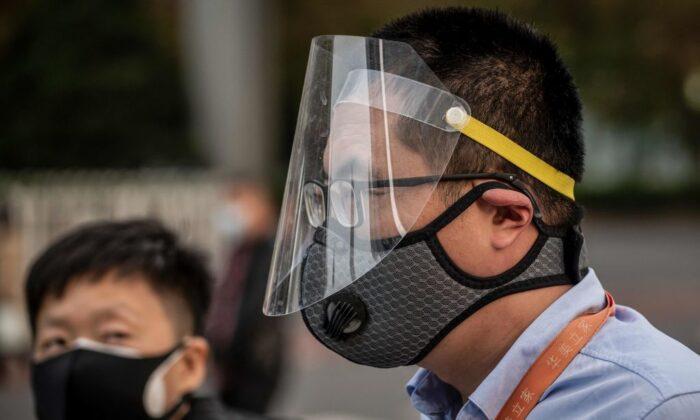 베이징의 러시아워 통근길에 마스크와 얼굴 가리개를 쓴 남성(오른쪽). 2020. 4. 7. | Nicolas Asfouri/AFP via Getty Images