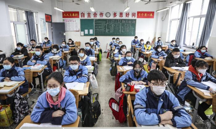 중공 바이러스 사태로 연기된 개학. 중국 장쑤성 화이안(華安) 학교 교실에 중고교 3학년 학생들이 앉아 있다. 2020. 3. 30. | STR/AFP via Getty Images