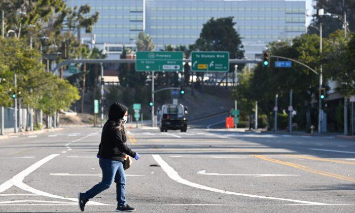 미국 캘리포니아주 로스앤젤레스 도심 로스앤젤레스 컨벤션센터 인근 빈 거리를 마스크를 쓴 한 여성이 건너고 있다. 2020. 3. 30. | Robyn Beck/AFP via Getty Images