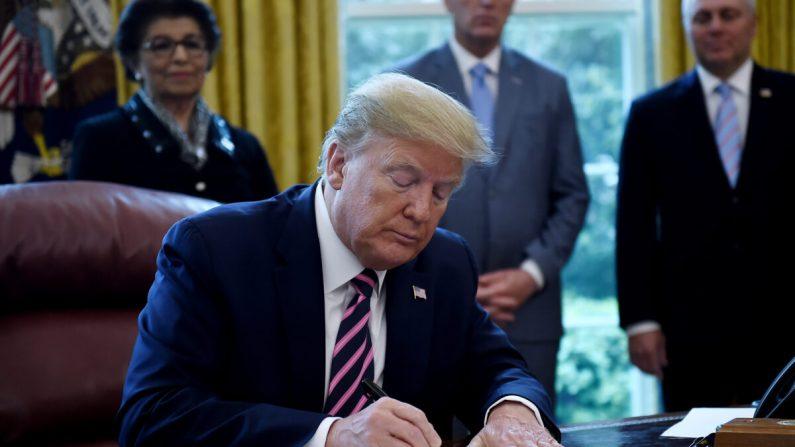 도널드 트럼프 대통령이 워싱턴 백악관 집무실에서 급여보호프로그램 및 건강관리 증진 법안에 서명하고 있다. 2020.4.24   Olivier Douliery/AFP via Getty Images
