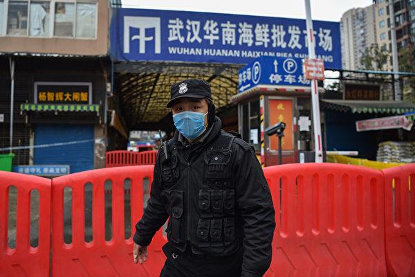 지난 1월 24일 중공 바이러스 발생지로 지목돼 폐쇄된 우한 화난수산시장 앞을 한 경찰이 지키고 있다. 그러나 이후 화난수산시장 발원설은 중국 당국에 의해 부인됐다. | AFP=연합뉴스