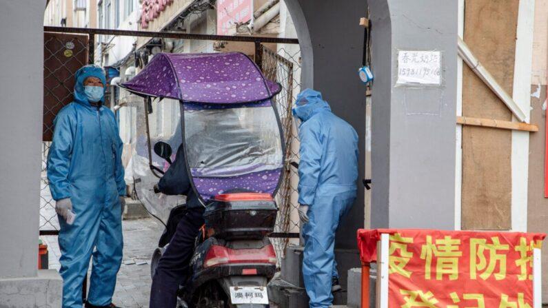 중국 지린성의 한 거주단지 입구에서 전신 방호복 차림의 사람들이 출입하는 주민들의 체온을 측정하고 출입기록을 작성하고 있다. | STR/AFP via Getty Images