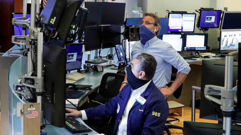 지난 5월 26일 대면업무가 재시작된 미국 뉴욕 증권거래소에서 트레이더들이 마스크를 쓴 채 일하고 있다.   REUTERS=연합뉴스
