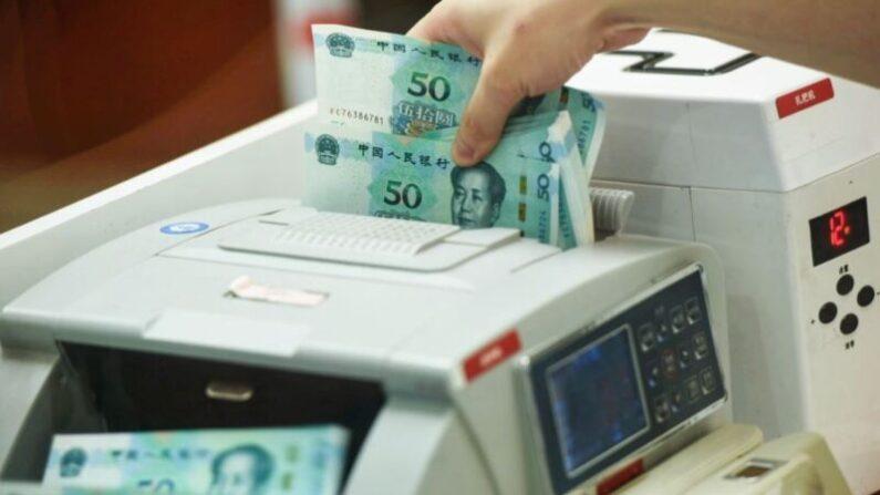 중국 저장성 항저우시의 한 은행에서 직원이 50위안권 지폐를 세고 있다. | STR/AFP via Getty Images