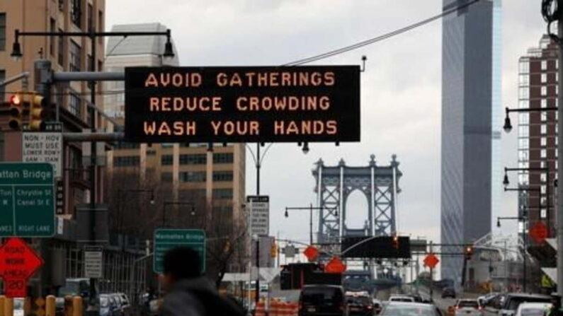지난 3월 20일(현지시간) 미국 뉴욕시 맨해튼브리지 입구에 설치된 전광판에 '모임을 피하라'는 안내문을 떠 있다.   로이터=연합뉴스
