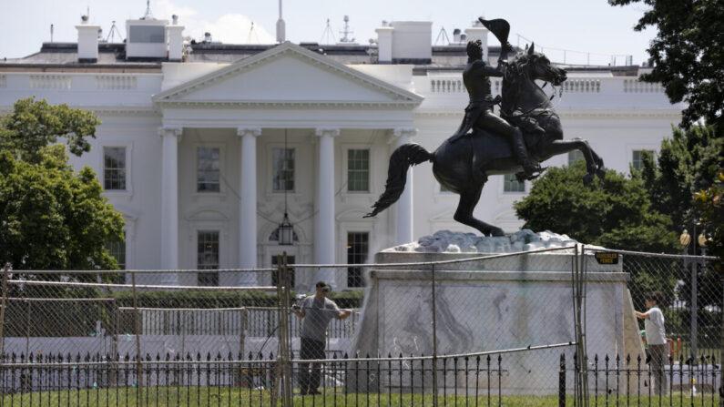 지난 24일 미국 워싱턴 백악관 바로 앞 라파예트 공원에 세워진 앤드루 잭슨 전 대통령 동상을 관리인들이 세척하고 있다.| AP=연합뉴스