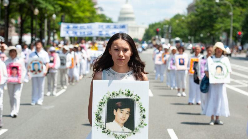 중국 공산정권의 박해로 숨진 파룬궁 수련자의 사진을 든 여성이 미국 워싱턴 DC에서 열린 7·20박해반대 행사에서 행진하고 있다. 2014.7.16 | 에포크타임스