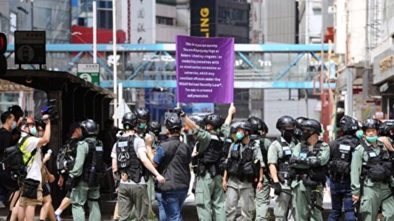 지난 7월 1일 홍콩 경찰이 시내에서 홍콩판 국가안전법 시행을 알리는 게시물을 들고 있다.   홍콩=에포크타임스