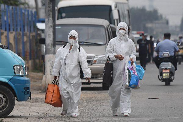지난 6월 13일 전신 방호복을 입은 여성 2명이 베이징 신파디 시장 부근을 지나고 있다.   GREG BAKER/AFP via Getty Images=연합뉴스