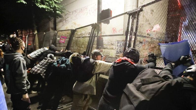 '흑인 생명도 소중하다(BLM)' 시위대가 오리건주 포틀랜드시 법원 청사 철책을 무너뜨리려 하고 있다. | AP=연합뉴스
