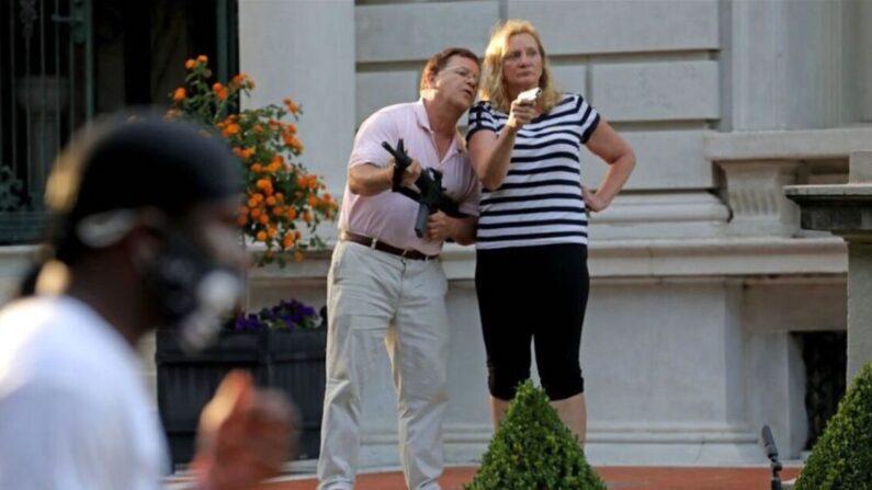 마크와 패트리샤 맥클로스키 부부가 미주리주 세인트루이스의 자택 앞에 총기를 들고 부근을 지나는 시위대를 경계하고 있다. 2020.6.28 | AP=연합뉴스