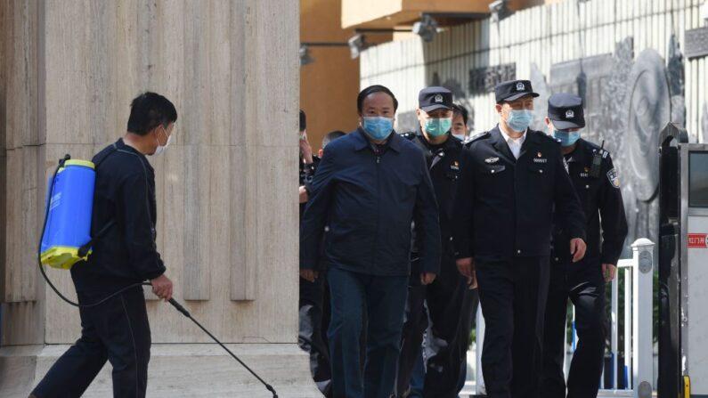 지난 4월 27일 중국 수도 베이징의 한 학교가 개학한 가운데 한 남성(왼쪽)이 교문 앞을 소독하고 있다. 그 오른편에는 경찰과 학교 관계자들이 학교를 빠져나오고 있다.   GREG BAKER/AFP=연합뉴스