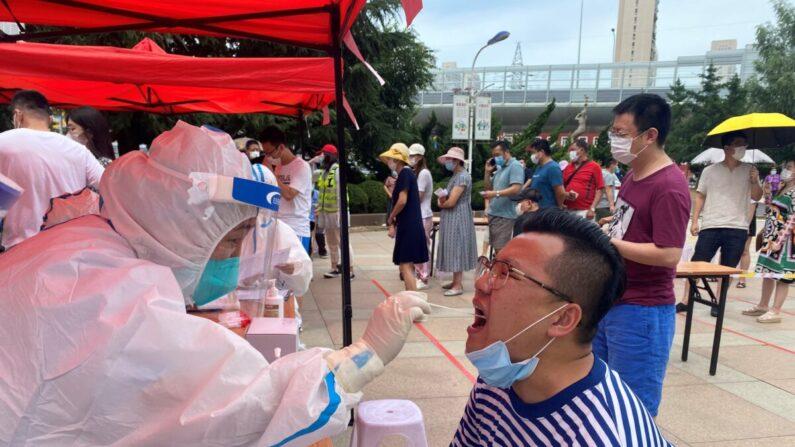 지난 6월 26일 중국 다롄시의 한 코로나19 임시 검진소에서 방역요원이 한 시민의 구강세포 표본을 채취하고 있다. | STR/AFP via Getty Images