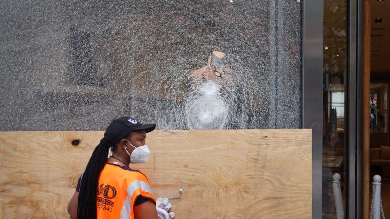 지난 10일, 전날 시위로 파손된 상점을 한 건축업체 직원이 수리하고 있다. |  Scott Olson/Getty Images