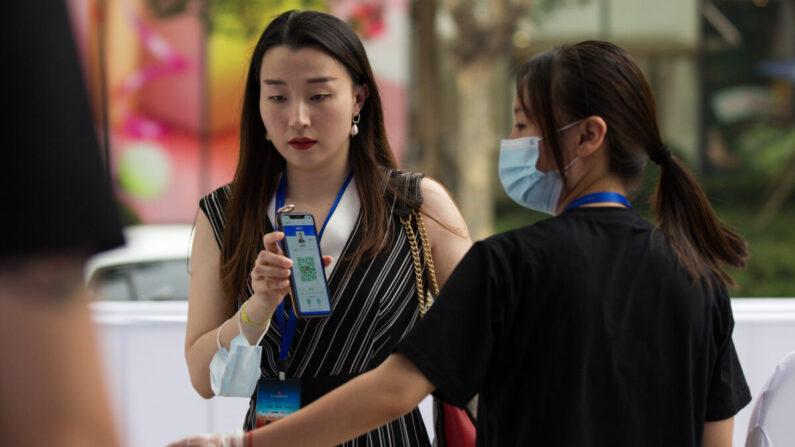 지난 7월 25일 중국 상하이국제영화제의 야외 상영 행사에 앞서 보호마스크를 착용한 한 진행요원이 입구에서 관객의 건강QR코드를 확인하고 있다. 상하이국제영화제는 7월 25일부터 8월 2일까지 진행됐다. | Yifan Ding/Getty Images