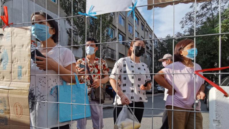 중국 랴오닝성 다롄시에서 중공 바이러스 신규 확진자가 나오면서 봉쇄된 주거단지 입구에서 주민들이 식료품이 배달되기를 기다리고 있다. 2020년 7월 23일 | 로이터=연합뉴스