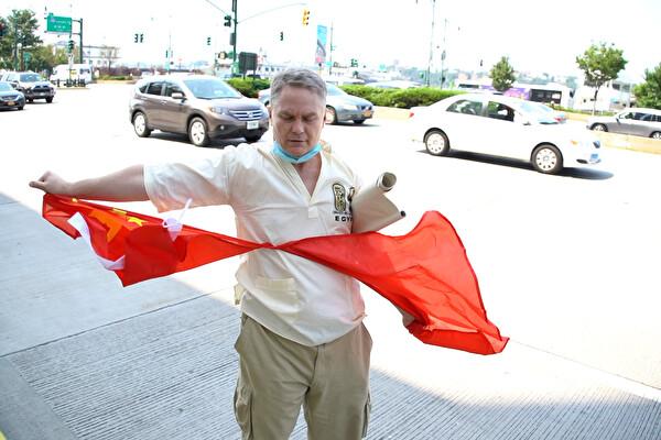 지난 8월 25일 미국 뉴욕 중국 영사관 앞에서 미국인 켄 깁슨 씨가 중국의 은폐 때문에 코로나19(중공 바이러스)이 확산됐다며 항의의 표시로 중국 공산당 깃발인 오성홍기를 찢고 있다.   에포크타임스