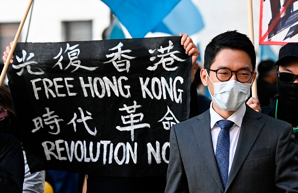 홍콩 민주화 운동가 네이선 로가 '자유 홍콩'이라고 적힌 현수막 옆에 서 있다. 그는 2020년 9월 1일 왕이 중국 외교부장과 독일 외무장관의 회담장소로 유력한 베를린의 외무부 건물 밖에서 열린 시위에 참석했다.   TOBIAS SCHWARZ/AFP via Getty Images